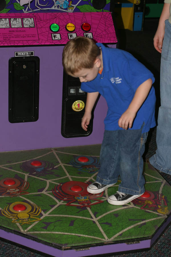 Mark stomping spiders [game at Chuck E. Cheese] (50mm, f/4.0, 1/60 sec, built-in flash)