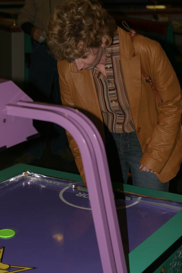 Mom playing air hockey [Chuck E. Cheese] (50mm, f/4.0, 1/60 sec, built-in flash)